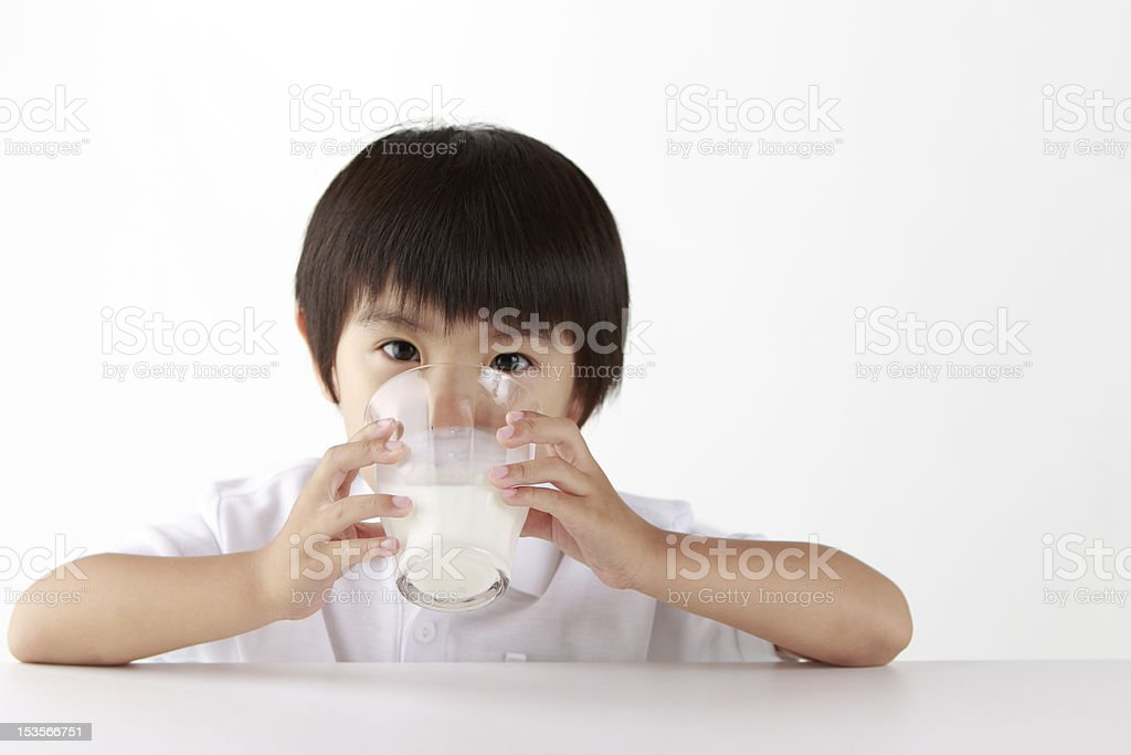 Asian boy drinking a transparent glass of milk royalty-free stock photo