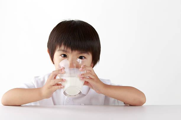 Asian boy drinking a transparent glass of milk stock photo
