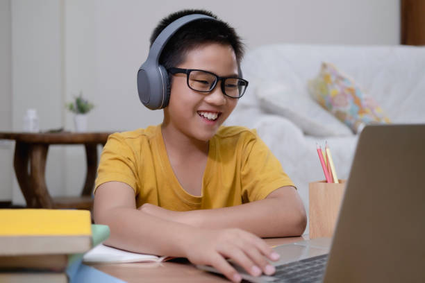 Asian boy enjoy self study with e-learning at home. Cheerfully boy excited using computer online learning schoolwork. Asian boy enjoy self study with e-learning at home. Online education and self study and homeschooling concept. elementary age stock pictures, royalty-free photos & images