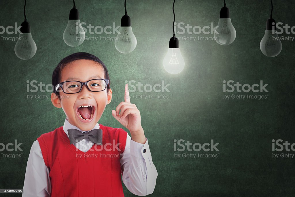 Asian boy has idea under light bulb in class stock photo
