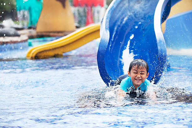 Asian boy having fun at swimming pool stock photo