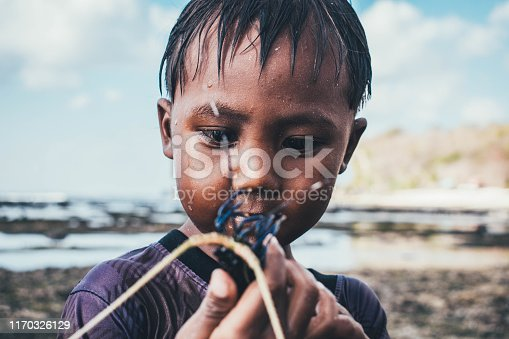 Asian Boy holding crab