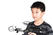 Asian boy holding hexacopter drone or quadrocopter toy in hand, studio shot isolated on white background.