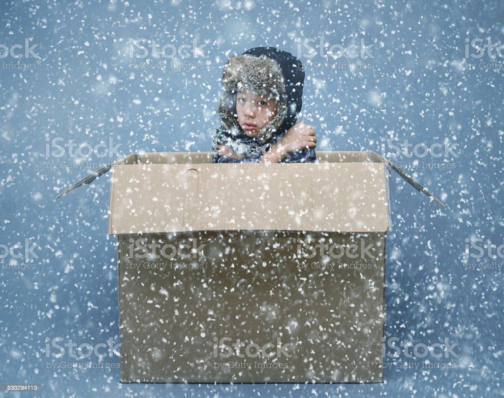 Asian boy in cardboard box during winter snowfall stock photo