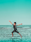 Asian boy is Jumping splashing water on a Beach for Children Summer Vacation happiness concept.