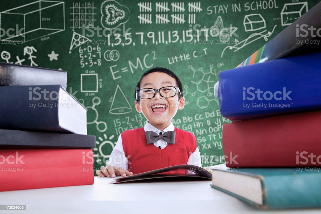Asian boy laughing in class with stack of books stock photo