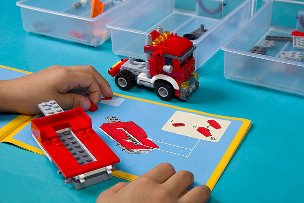 Asian boy learns to build lego following instruction manual stock photo