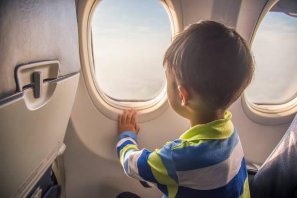 garçon asiatique à la recherche d'une vue aérienne du ciel et les nuages en dehors de la fenêtre de l'avion en position assise sur avion. - nuage 6 photos et images de collection