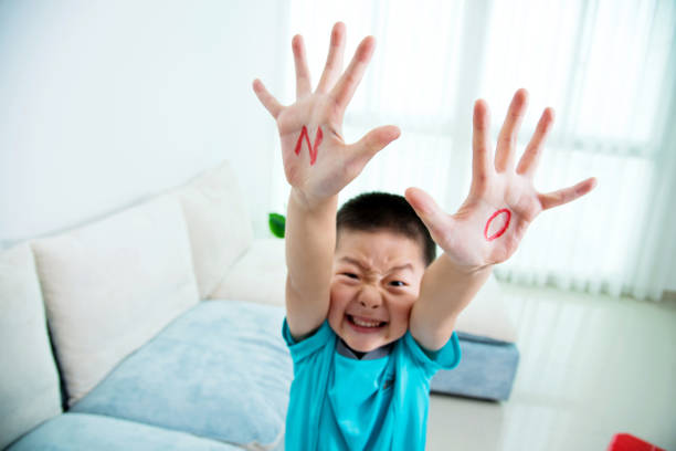 Asian boy makes a stop gesture Asian boy makes a stop gesture. single word no stock pictures, royalty-free photos & images