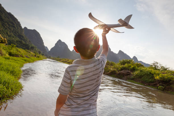 Asian boy playing with model plane outdoors stock photo