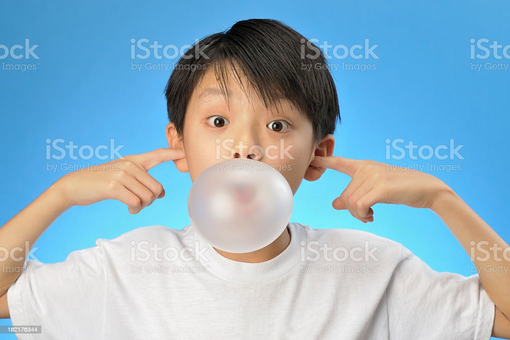Asian boy plugging his ears and blowing a bubble royalty-free stock photo