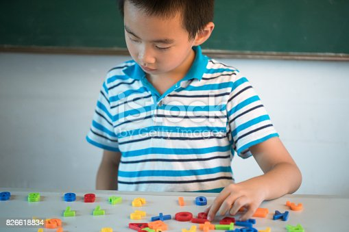 istock asian boy sitting infront of blackboard with numbers 826618834