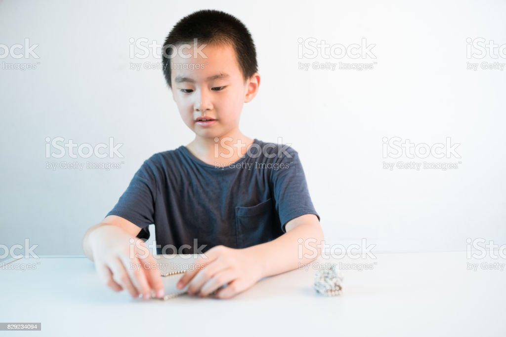 Asian boy sitting infront of table playing magnetic beads stock photo