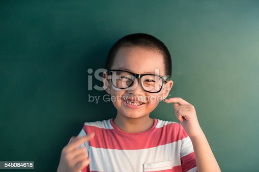 istock asian boy standing infront of chalkboard 545084618