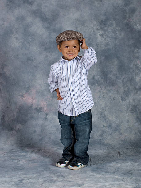 Asian Boy Standing School Pose Hands on Hat stock photo