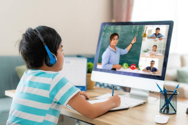 asian boy student videokonferenz e-learning mit lehrern und klassenkameraden am computer im wohnzimmer zu hause. homeschooling und fernunterricht, online, bildung und internet. - homeschooling stock-fotos und bilder