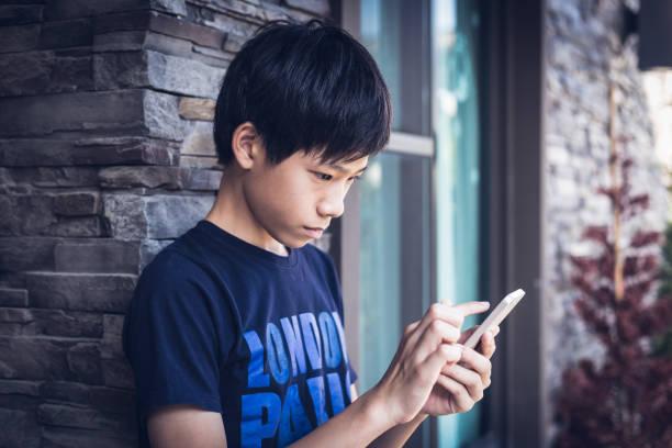 Asian boy teenager using smartphone, outdoor daylight. stock photo