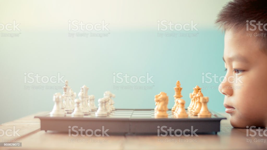 asian boy think or plan about chess game selective focus vintage...