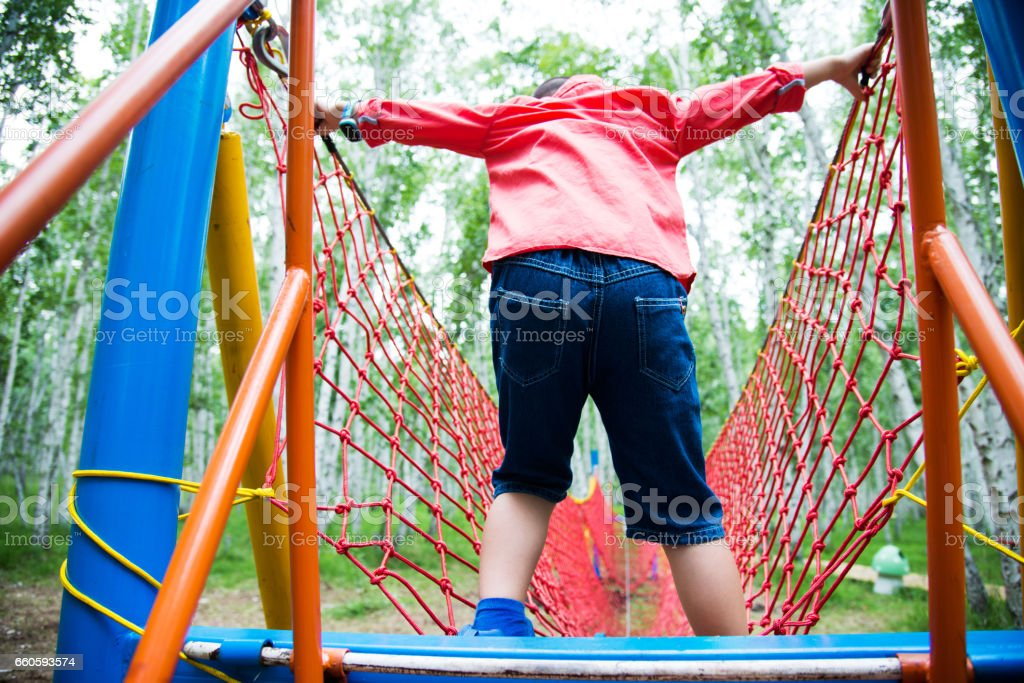 Asian boy walking on rope bridge royalty-free stock photo
