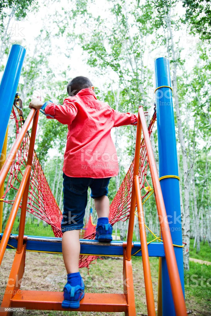 Asian boy walking on rope bridge stock photo