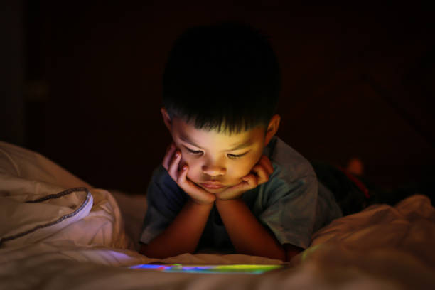 Asian boy watching colorful bright tablet screen in dark. stock photo