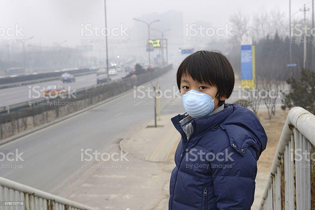 Ragazzo asiatico con la bocca maschera contro l'inquinamento dell'aria (Pechino) - foto stock