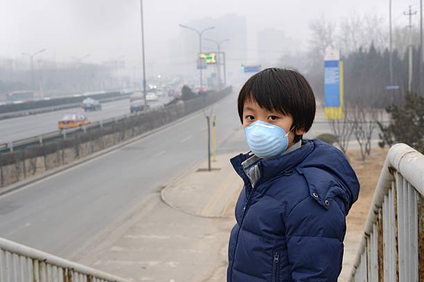 rapaz asiático vestindo máscara oral contra a poluição do ar (pequim) - boca suja imagens e fotografias de stock