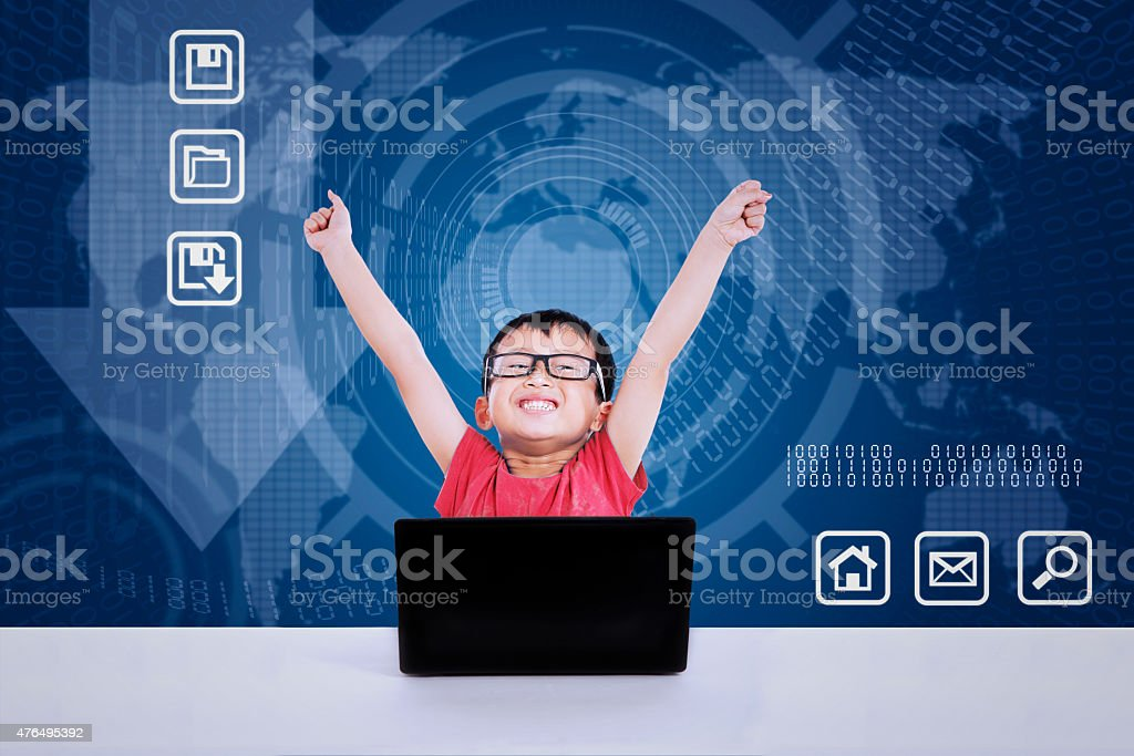 Asian boy winning using laptop on blue background stock photo