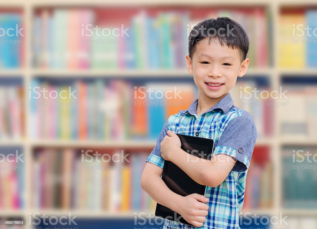 Asian boy with tablet computer in school library stock photo