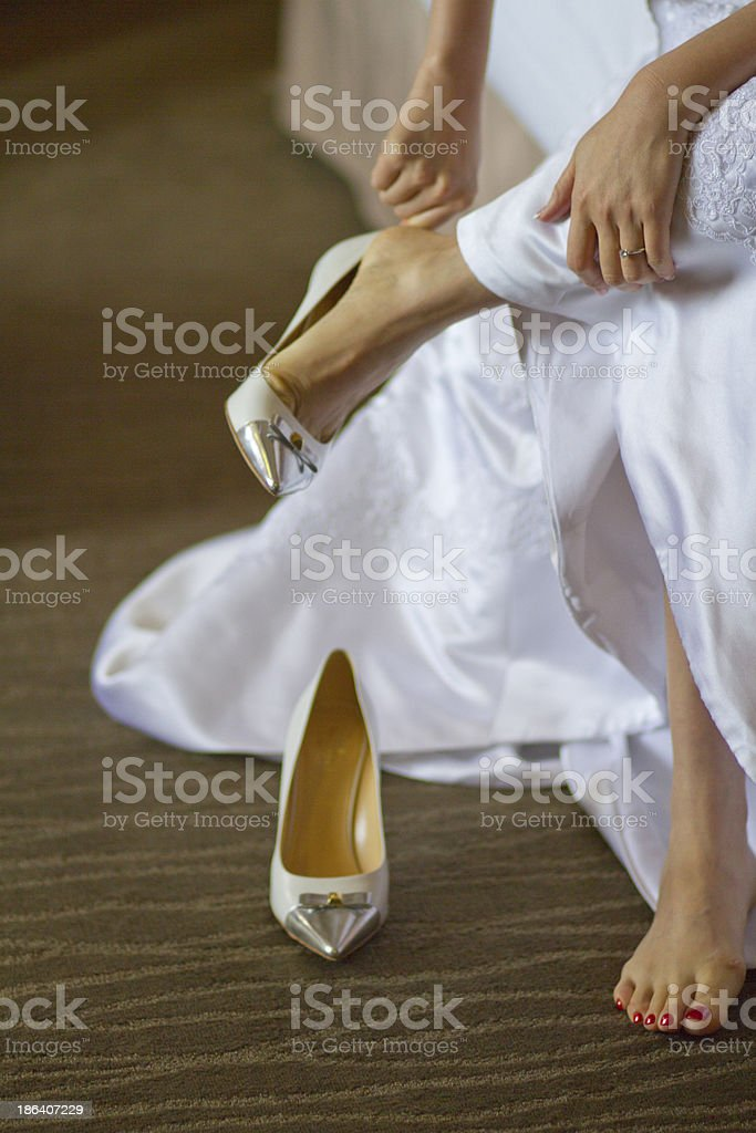 Asian bride dressing up the wedding shoes.. royalty-free stock photo