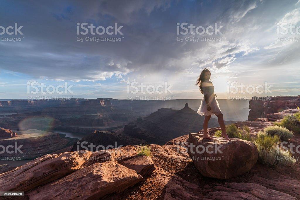 Asian bride posing over vast canyons of Utah desert, Moab. stock photo