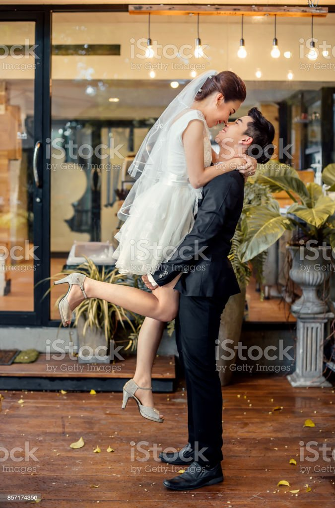 Asian bridegroom holds Asian bride up to height and is about to kiss each other in romantic feeling. stock photo