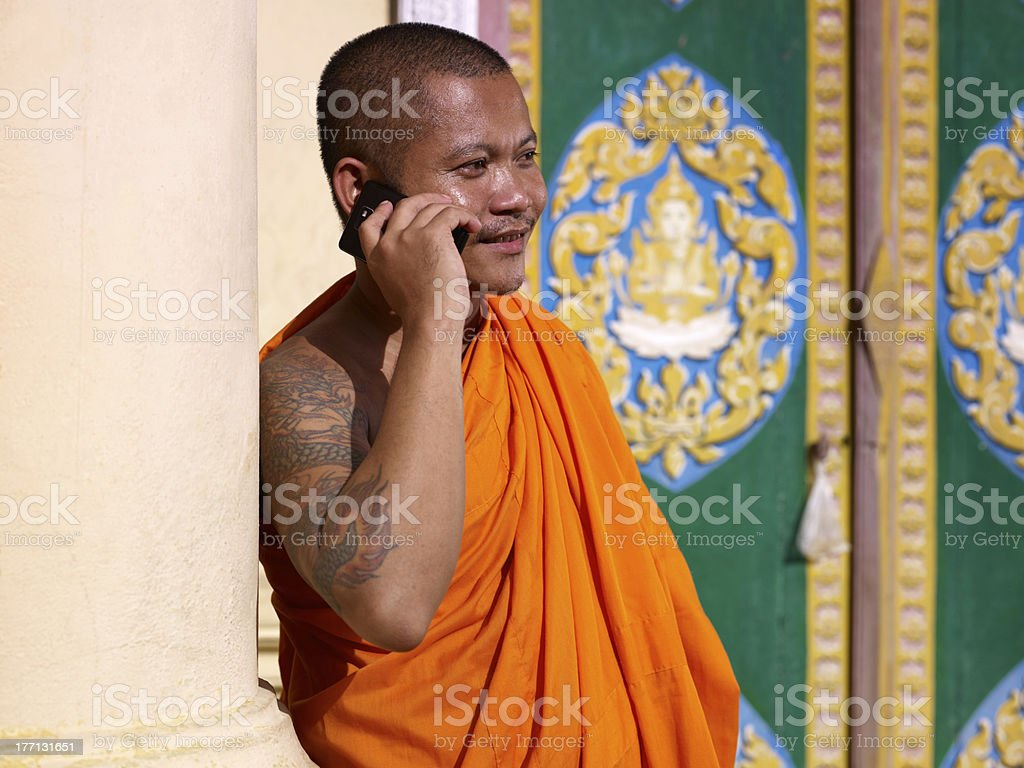 Asian buddhist monk talking with mobile phone in temple royalty-free stock photo