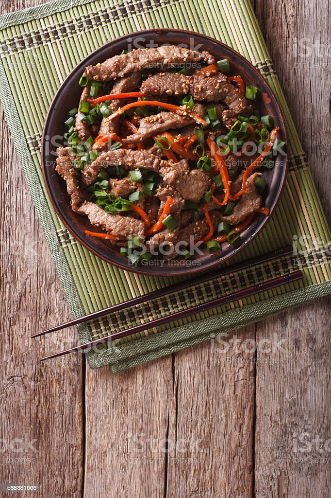 Asian Bulgogi beef slices fried with sesame on plate. vertical stock photo