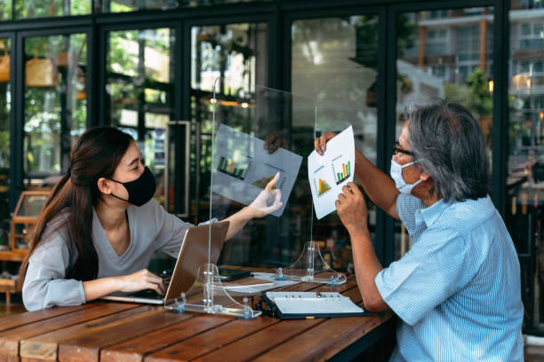 Asian business man and woman discussing in coffee shop with masks on stock photo