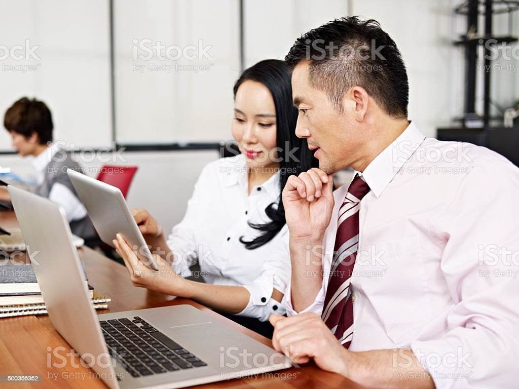 asian business man and woman working in office stock photo