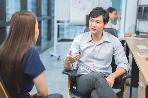 Asian Business Man discusión y escuchar las respuestas de los candidatos, concepto de entrevista de trabajo. Gente feliz de negocios hablando sobre la reunión en la oficina - foto de stock