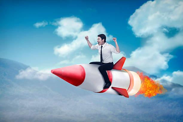 asian business man flying ride rocket stock photo