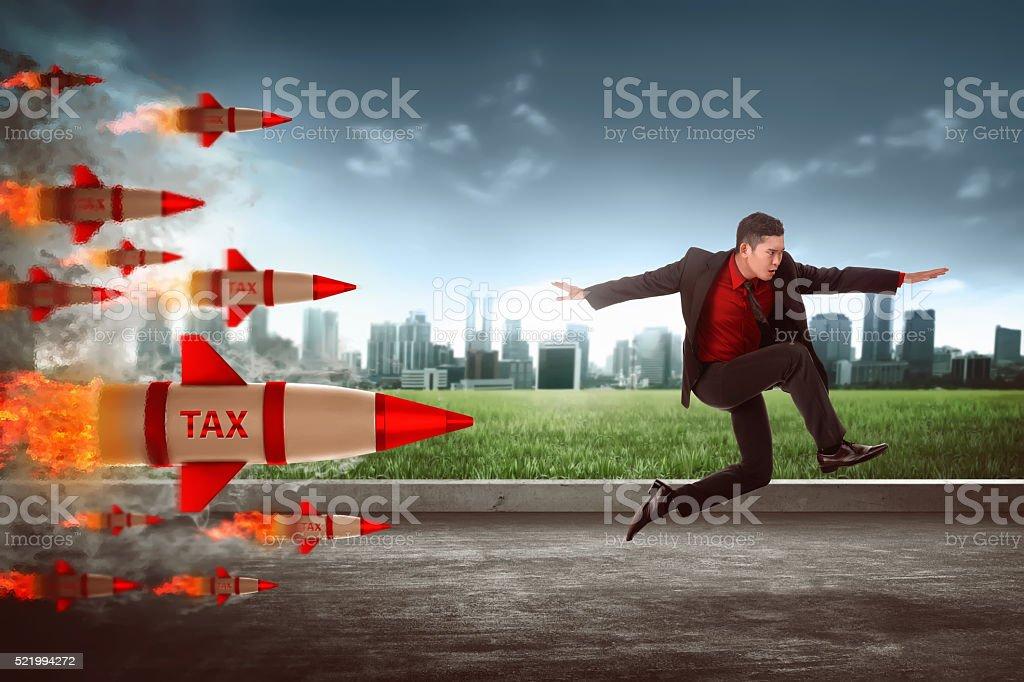 Asian business man jump from tax rocket stock photo