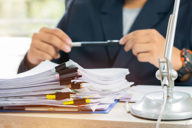 Asian Business man Manager sitting hold pen for signing applicant filling documents reports papers company application form or registering claim on office. Document Report and business busy Concept stock photo