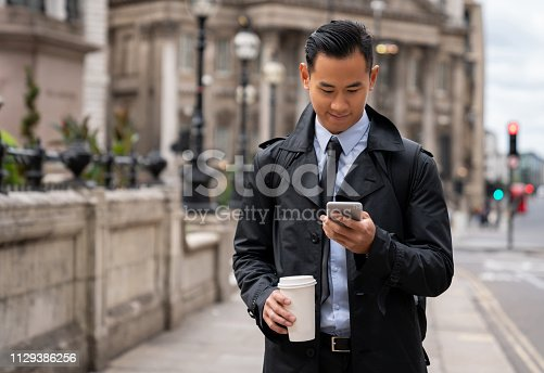 Portrait of a successful Asian business man using cell phone and drinking coffee on the street - morning routine concepts
