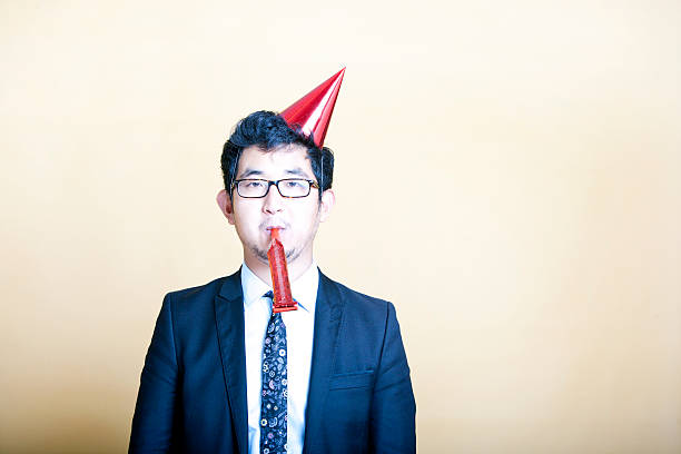 Asian business man wearing party hat stock photo