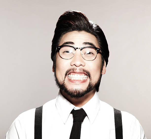 Asian business man with a goofy smile on his face Goofy young Asian man in business attire and suspenders wearing glasses smiling at camera.  Square framed shot. desaturated stock pictures, royalty-free photos & images
