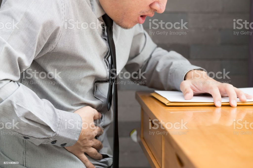Asian business man with stomachache in office stock photo