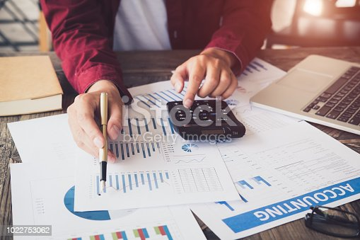 istock asian business man working with hand pointing graph discussion and analysis data charts and graphs and using a calculator to calculate numbers.Business finances and accounting concept 1022753062