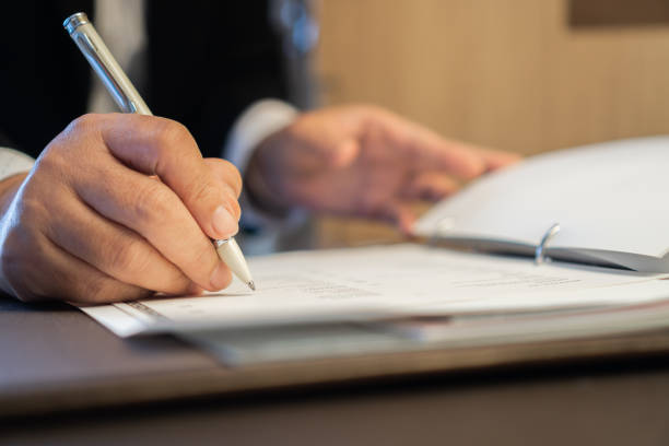 Asian Business people Manager checking and signing applicant filling documents reports papers company application form or registering claim on desk office. Document Report and business busy Concept stock photo