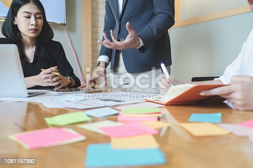 1127866562 istock photo Asian business people meeting with new startup project pointing graph discussion and analysis data charts and graphs.Business finances and accounting concept 1091197392