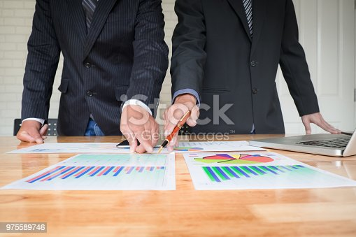 927401824 istock photo Asian business people meeting with new startup project pointing graph discussion and analysis data charts and graphs.Business finances and accounting concept 975589746