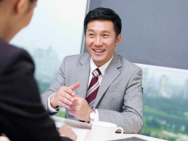 asian business people asian businessman discussing business with colleague in office, looking excited. click for more: korean ethnicity stock pictures, royalty-free photos & images