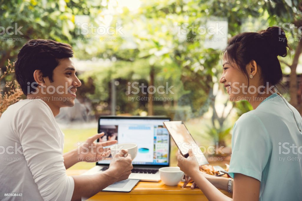 Asian business people  talking about at the coffee shop cafe. stock photo
